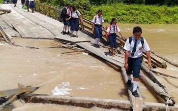 JEMBATAN RUSAK - Sejumlah murid sekolah melintasi jembatan penghubung Desa Tumbang Miwan menuju Desa Tewang Pajangan di Kecamatan Kurun yang rusak, Selasa (24/1/2017). BORNEONEWS/EPRA SENTOSA