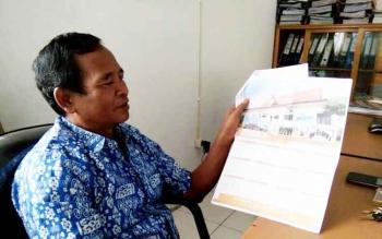 Komisioner KPUD Lamandau bidang sosialisasi, Andreas Nahan, saat menunjukkan contoh Kalender Informasi Pilkada Lamandau 2018, kepada Borneonews, Selasa (24/1/2017) siang. BORNEONEWS/HENDI NURFALAH