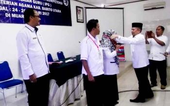 Kepala Kantor Kementerian Agama Kabupaten Barito Utara Tuaini Ismail menyematkan tanda peserta diklat subtantif peningkatan kompetensi instrumen penilaian guru secara simbolis, Selasa (24/1/2017). (BORNEONEWS/RAMADHANI)