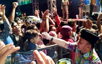 Gubernur saat menyuapi salah satu anak yang menyaksikan hiburan rakyat pada HUT ke-12 Kecamatan Pangkalan Banteng.