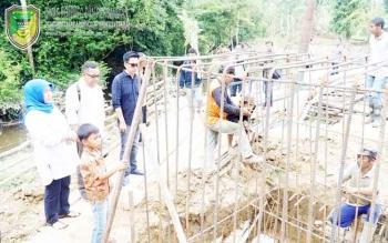 Bupati Barito Utara, Nadalsyah dsaat meninjau pembangunan jembatan Desa Teluk Malewai, Sabtu (28/1/2017).
