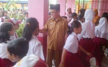 Patejab Bupati Barsel, Mugeni bersalaman dengan murid SD Buntok IX seusai upacara bendera, Senin (30-1-2017).