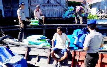 Anggota Sat Polair Polres Sukamara saat memantau aktivitas warga yang mengangkut sembako melalui jalur perairan.