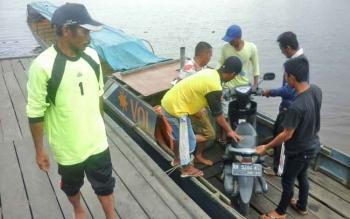 Beberapa pekerja buruh pelabuhan membantu pemilik usaha angkutan sungai jenis longboat menaikkan kendaraan bermotor ke perahu penumpang, Selasa (31/1/2017).