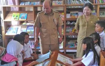 Kepala Dinas Perpustakaan dan Kearsipan Kabupaten Gunung Mas, Yokdie (kiri) saat memantau anak didik sedang membaca, Selasa (31/1/2017).