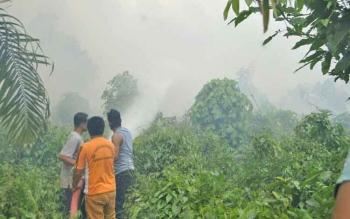 Petugas Damkar dibantu warga tengah memadamkan api di lahan terbakar di daerah Nanga Bulik, beberapa waktu lalu.