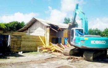 Alat berat milik Pemerintah Kabupaten Kotawaringin Barat menghancurkan bangunan di lokasi prostitusi simpang kodok.
