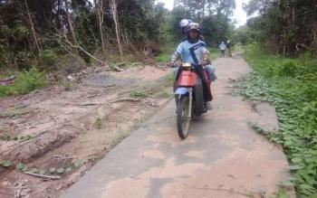 Dua warga Sungai Perlu berkendara melintasi di jalan semenisasi tak jauh dari lokasi pelabuhan Segintung yang dibangun menuju ke arah desa mereka. BORNEONEWS/PARNEN