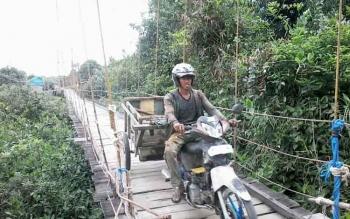 Warga dengan sepeda motor gerobaknya tampak melintasi jembatan gantung yang melintang di Sungai Kelanaman Desa Telangkah, Rabu (1/2/2017).