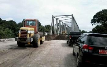Sebuah alat berat tampak menjalankan pekerjaan di Jembatan Kelanaman Kasongan, Rabu (1/2/2017).