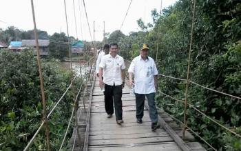 Sekda Katingan Nikodemus (kanan pakai topi) didampingi Kepala Dinas Pekerjaan Umum Alyono berjalan di jembatan gantung Sungai Kelanaman Desa Telangkah, Rabu (1/2/2017).