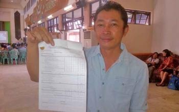 Komisioner KPU Barito Selatan Bahruddin menunjukan salah satu formulir yang dipasang pengaman hologram.