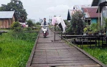 Pengendara melintas di jembatan titian yang berlubang. Warga mengancam, apabila 2017 ini belum juga diperbaiki ia akan turun ke DPRD untuk menyampaikan secara langsung.