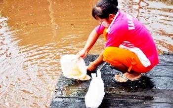 Seorang warga Desa Sungai Sekonyer menggunakan air kanal di desanya untuk kebutuhan sehari-hari, bahkan memasak.