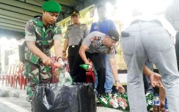 MUSNAHKAN - Anggota Polres Kobar dan Kodim 1014/PBN tengah menghancurkan ratusan botol minuman keras di halaman depan Mapolres Kobar.