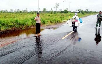 Anggota Polsek Kahayan Tengah saat mengatur lalulintas di titik jalan yang terendam banjir di Desa Penda Barania, Rabu (1/2/2017).
