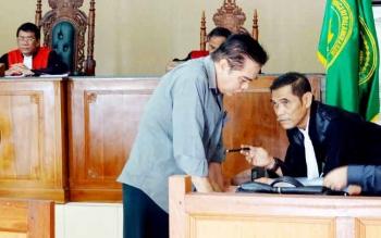 SIDANG KORUPSI - Henry Singarasa berdiskusi denga Penasehat Hukumnya Bachtiar Effendy seusai jaksa membacakan surat dakwaan, Kais (2/2/2017).