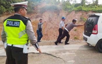IPTU Hermanto Kasat Lantas Polres Gunung Mas ikut mendorong mobil yang tidak mampu menaiki tanjakan di jalan rusak ruas Kuala kurun- Palangka Raya, Jumat (3/2/2017)