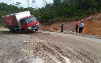 Sebuah truk dengan susah payah melintasi titik yang rusak parah di ruas Jalan Kuala Kurun - Palangka Raya, Jumat (3/2/2017)