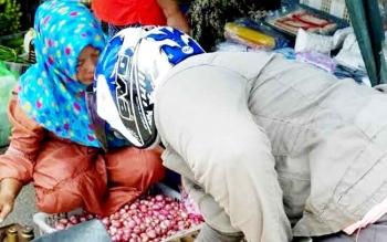 Seorang warga tawar menawar harga bawang di Pasar Kereng Pangi Kabupaten Katingan, Minggu (5/2/2017).