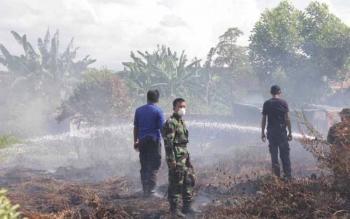 Petugas memadamkan kebakaran lahan yang terjadi di Kotim, beberapa waktu lalu.