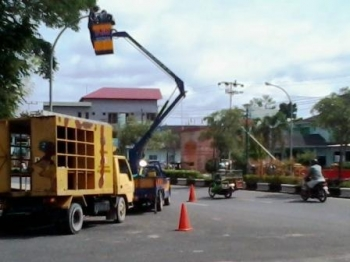 Petugas PLN memperbaiki Lampu Penerangan Jalan Umum (PJU)
