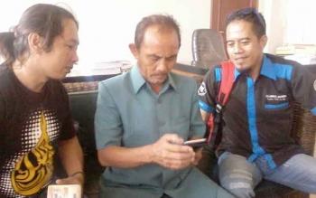 Bhakti Gunawan (rengah) anggota DPRD Kabupaten Katingan menunjukkan gambar di HP-nya terkait jalan di wilayah hulu, Senin (6/2/2017).