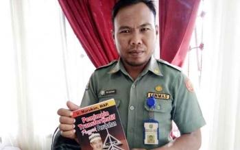 Kasubag Protokol Setda Lamandau, Tri Santoso, saat menunjukkan Buku yang akan di launching.