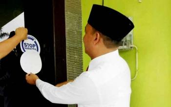 Wakil Bupati Sukamara yang juga Ketua BNK Sukamara, Windu Subagio saat memasang stiker stop narkoba di jendela kantor LPTQ Sukamara.