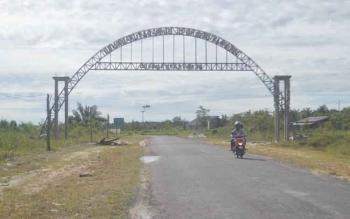 Salah satu kendaraan roda dua melintas di gapura Desa Karta Mulya Kecamatan Sukamara Kabupaten Sukamara.
