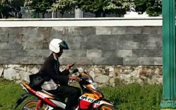 Tampak salah satu pengendara sepeda motor saat menggunakan alat komunikasi di Jalan Iskandar Pangkalan Bun.