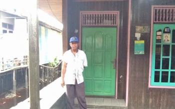 Abdul Rifai, warga Kumai Hilir berdiri di depan pintu rumah TKP pembunuhan Normawati, Rabu (8/2/2017) sore. Warga digegerkan dengan penampakan sosok mirip Normawati tengah menarik selimut di dalam rumah.