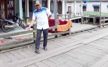Anggota DPRD Kapuas Nordin memperlihatkan kondisi jembatan ulin di dalam Kota Palingkau, Kecamatan Kapuas Murung, yang rusak.