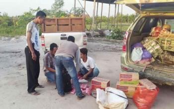 Anggota Polsek Rakumpit menggeledah barang bawaan Irfan Arifin (kaos putih duduk).