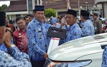 Bupati Barito Utara Nadalsyah didampingi Kepala Dinas Kesehatan Robansyah menyerahkan secara simbolis mobil ambulans kepada perwakilan puskesmas.