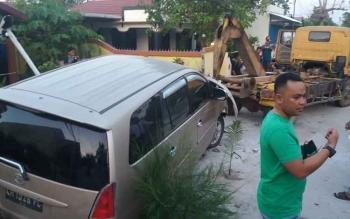 Kondisi mobil Inova yang manbrak pagar rumah warga di Jalan Gatot Subroto, Sampit saat hendak di evakuasi, Sabtu (11/2/2017).