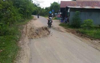 JALAN RUSAK : Seorang pengendara sepeda motor melintas di Jalan Damang Gaman Kuala Kurun yang rusak. Kerusakan jalan itu berpotensi membahayakan pengendara.