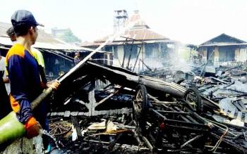 Petugas Damkar beraksi memadamkan api dalam musibah kebakaran di pemukiman padat penduduk, Flamboyan Bawah, persisnya belakang Anline foto, Jalan A Yani, Palangka Raya, Minggu (12/2/2017).