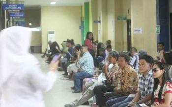 Sejumlah pasien pengguna BPJS Kesehatan antre berobat di ruang tunggu poliklinik Rumah Sakit Sultan Imanudin, Pangkalan Bun, Kabupaten Kotawaringin Barat.