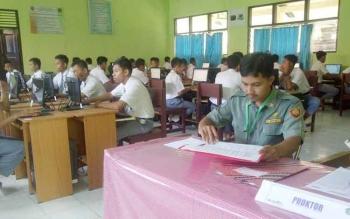 Seorang guru di salah satu SMA di Sampit, Kotim, mempersiapkan materi pelajaran komputer. Kurangnya guru berstatus pegawai negeri membuat keberadaan guru kontrak sangat dibutuhkan.