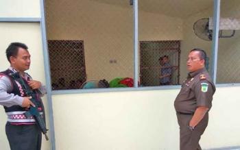 Kepala Kejaksaan Negeri Palangka Raya Eduard Sianturi berkomunikasi dengan Anggota Sat Sabhara Polres Palangka Raya Bripka Kusmayanto saat memeriksa ruang tahanan, Selasa (14/2/2017).