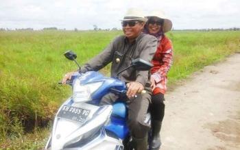 Bupati Seruyan Sudarsono dan istri Ratna Mustika saat menaiki kendaraan bermotor untuk menuju lokasi penanaman padi bersama di Desa Mekar Indah, Kecamatan Seruyan Hilir Timur, Selasa (14/2/2017).