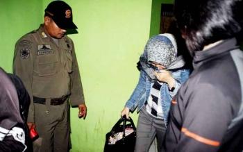 Seorang wanita menutup wajah dengan kain saat tertangkap di razia yang digelar Satpol PP Kotim, karena berduaan dengan seorang lelaki bukan muhrim di kamar hotel.