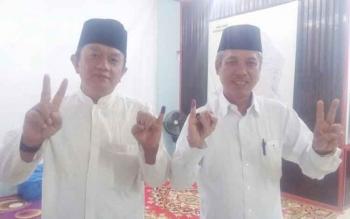 Indrawan Sakti (kiri) dan pasangannya Noorhanuddin (kanan) menunjukan jari manisnya yang sudah diolesi tinta bukti sudah malakukan pencoblosan surat suara dalam Pilkada Kobar Rabu (15/2/2017).