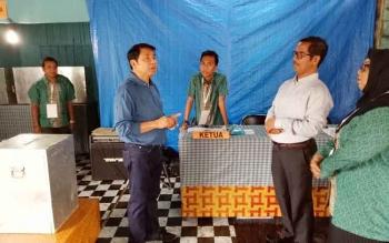 Haji Abdul Rasyid (baju biru) berbincang dengan petugas TPS 3 Kelurahan Mendawai, Pangkalan Bun.