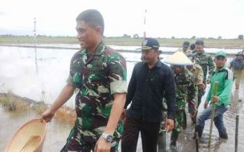 Danrem 102/Pjg Kolonel Arm M. Naudi Nurdika (depan) saat melaksanakan tanam padi bersama di Desa Mekar Indah, Selasa (14/2/2017).