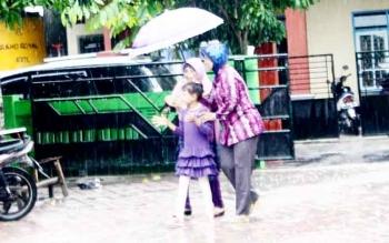 Meski hujan mengguyur, warga tetap menggunakan hak pilihnya. Mereka datang ke TPS menggunakan payung, Rabu (15/2/2017).