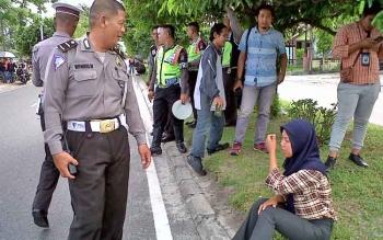 Remaja putri ini terduduk sambil mengusap air matanya lantaran ditilang polisi, Kamis (16/2/2017)