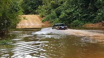 Sebuah mobil melintasi ruas jalan penghubung Tumbang Miri dan Tumbang Napoi yang terendam banjir.