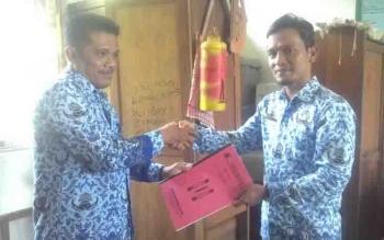 Kepala SDN 3 Sei Lunuk menyerahkan proposal perbaikan bangunan sekolah ke Camat Bataguh, Budi Kurniawan (kanan).